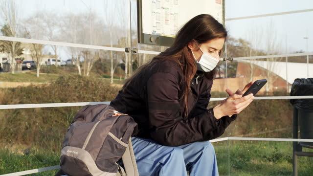 vídeos y material grabado en eventos de stock de trabajador sanitario viajando a casa y esperando el autobús. - un día en la vida