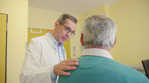 healthcare worker consoling patient at clinic - males stock videos & royalty-free footage