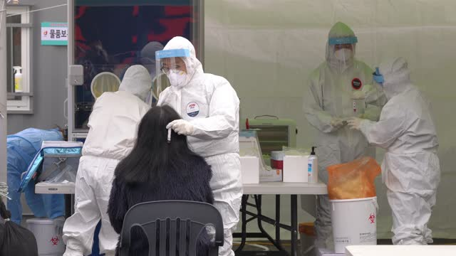 healthcare worker dressed in a protective suit collects samples from a woman at a temporary covid-19 testing site in front of seoul station on... - 朝鮮半島点の映像素材/bロール