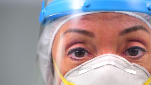 stockvideo's en b-roll-footage met zorgverlener gezicht tijdens coronavirus covid 19 nieuwe corona virus uitbraak - operatiemasker