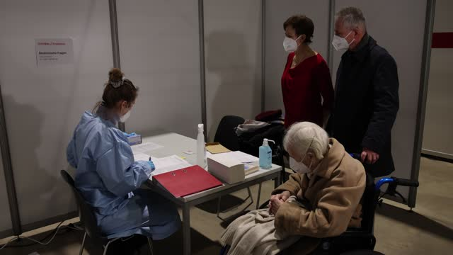 healthcare worker gives information about pfizer/biontech vaccine against covid-19 to an elderly woman at a vaccine center in the state of saxony... - senior women stock videos & royalty-free footage