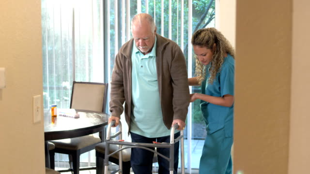 healthcare worker helping senior man with walker - dining room stock videos & royalty-free footage