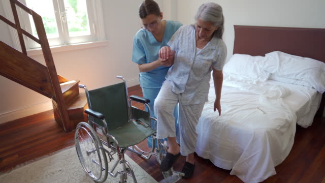 healthcare worker helping senior woman to sit in wheelchair - female nurse stock videos & royalty-free footage