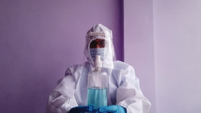 healthcare worker holding a spray bottle of disinfectant sanitizer for home and personal use recommended for fighting the deadly against the global pandemic - full suit stock videos & royalty-free footage
