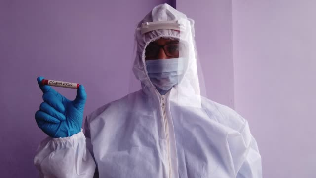 healthcare worker in a full protective gear with a positive result coronavirus positive test tube facing the camera during the global pandemic crisis worldwide - full suit stock videos & royalty-free footage