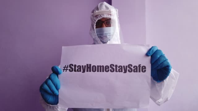 healthcare worker in full body suit holding a sign in front of camera requesting people to stay at home for protection and safety as they battle the global pandemic crisis worldwide - full suit stock videos & royalty-free footage