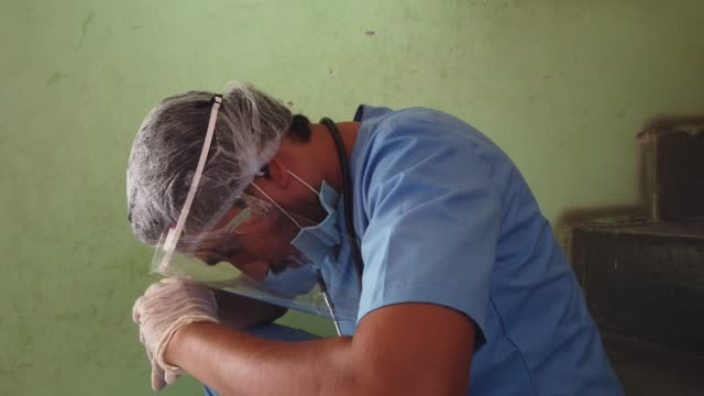 vídeos y material grabado en eventos de stock de healthcare worker is exhausted and completely drained as he takes a few moments off his hectic overtime long odd hours of continuous work at the frontline of defeating the global pandemic - trabajador de primera línea