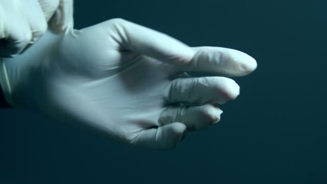 healthcare worker putting on medical gloves - latex glove stock videos & royalty-free footage
