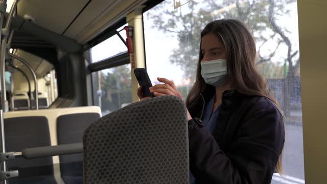 vídeos de stock e filmes b-roll de healthcare worker riding a bus home. - transporte público