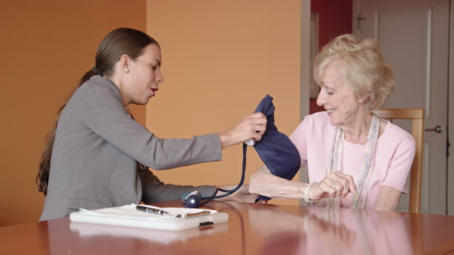 healthcare worker takes blood pressure of senior woman - house call stock videos & royalty-free footage