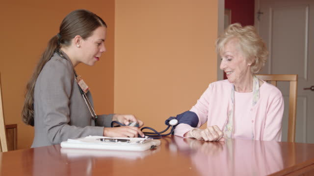 healthcare worker takes blood pressure of senior woman - hypertension stock videos and b-roll footage