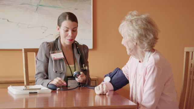 healthcare worker takes blood pressure of senior woman - medical record stock videos & royalty-free footage