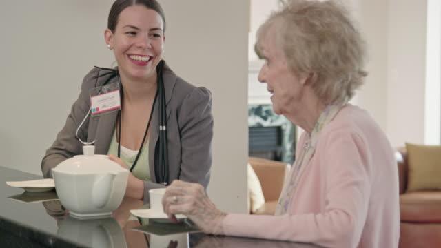 vídeos y material grabado en eventos de stock de trabajador profesional de la salud hablando con altos mujer café - hacer un descanso
