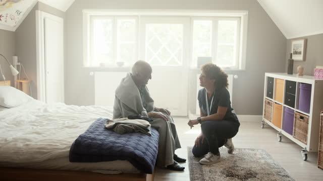 healthcare worker talking with senior man - bathrobe stock videos & royalty-free footage