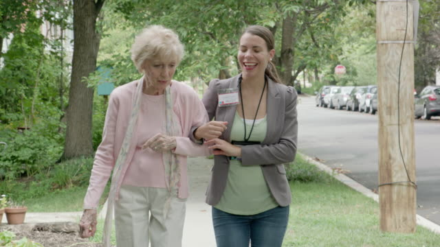 healthcare worker walking with senior woman outdoors - assistance stock videos & royalty-free footage