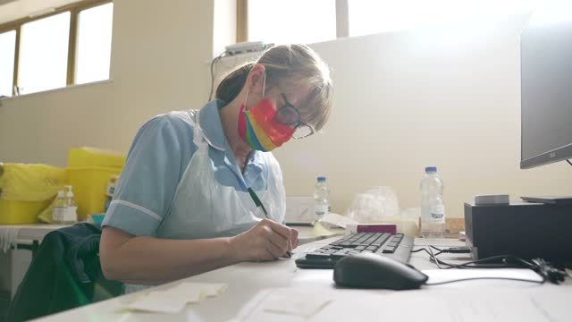 healthcare worker wears a rainbow mask at a vaccination centre for the astrazeneca/oxford university covid-19 vaccine on march 25, 2021 in bedford,... - spectrum stock videos & royalty-free footage