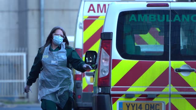 healthcare worker wears ppe next to a row of ambulances outside the emergency department of the royal london hospital in london, england, on january... - slow motion stock videos & royalty-free footage