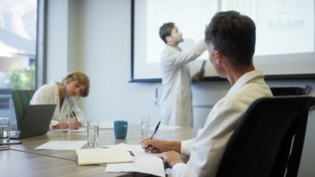 healthcare workers in board room during meeting - tavolo da conferenza video stock e b–roll
