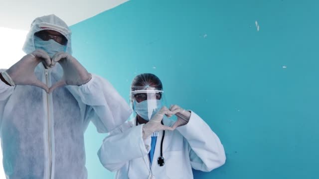 vídeos de stock e filmes b-roll de healthcare workers looking at camera, man and woman, and assuring confidence and positive emotions by greeting, making heart shape and waving goodbye after hours of work - fato