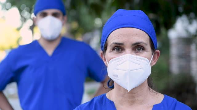 vídeos de stock, filmes e b-roll de profissionais de saúde olhando para a câmera usando máscaras n95 protetoras - profissional da área médica