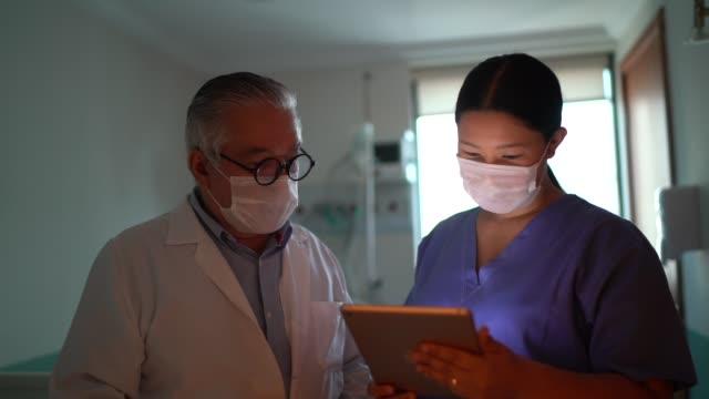 vídeos y material grabado en eventos de stock de trabajadores sanitarios que usan tabletas digitales con mascarilla facial en el hospital - sección hospitalaria