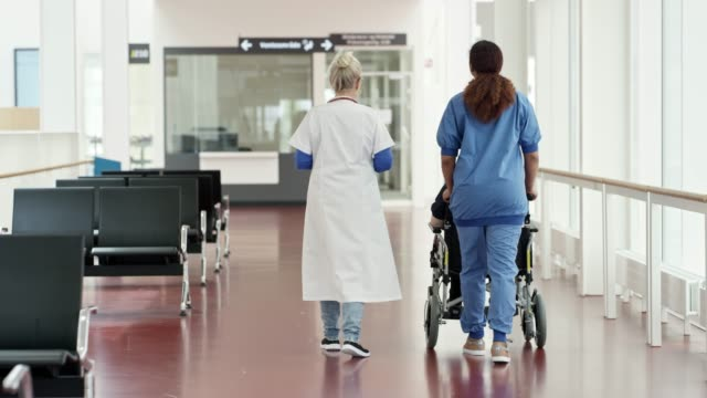 healthcare workers with patient on wheelchair - pushing stock videos & royalty-free footage