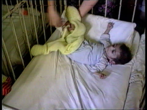 Romanian Orphans Fund Raising INT ROMANIA TCMS Small child being rocked by worker in TX orphanage ITN TCMS Child in cot having clothes removed