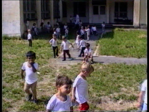 vidéos et rushes de romanian orphans fund raising romania tms children playing in grounds of tx orphanage itn ts boy in orphanage ext tms woman in room full of cots... - orphelin