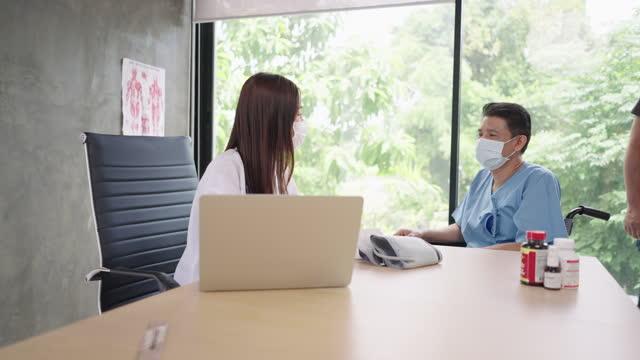 vídeos de stock, filmes e b-roll de médico idoso da saúde reunião médico com ajuda para um enfermeiro do sexo masculino durante covid-19 com máscara facial protetora, visão lateral - 20 29 years