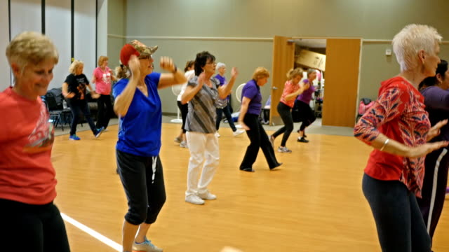 Healthy active seniors dance in exercise class
