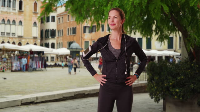 stockvideo's en b-roll-footage met healthy active woman jogger in venice smiling directly at camera - jogster
