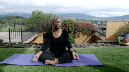 Healthy African American senior sitting cross legged meditating outside