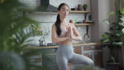 Healthy asian yoga woman doing yoga in tree pose at home