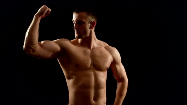 healthy athlete shows good muscle on black background - torso stock videos & royalty-free footage