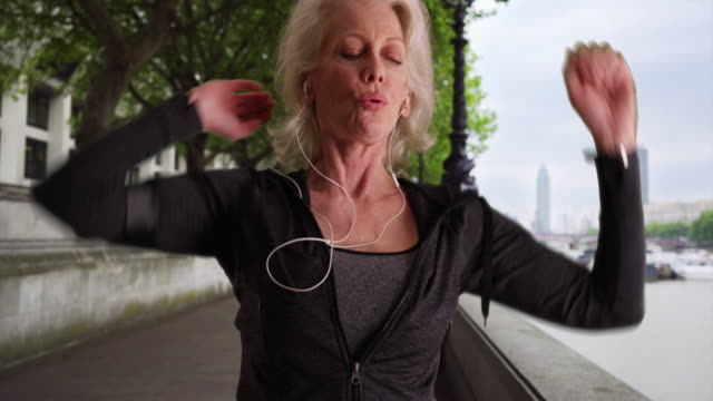 stockvideo's en b-roll-footage met healthy athletic older woman warms up for jog in the city - jogster