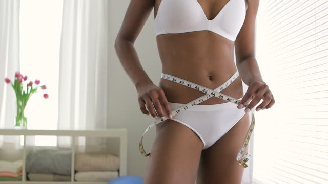 healthy black woman measuring waist on diet - waist stock videos & royalty-free footage