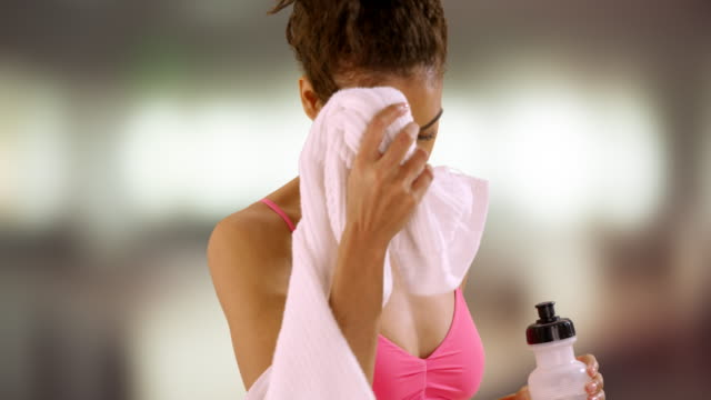 healthy black woman wiping face with towel.  portrait of black woman taking a break from exercise, drinking water bottle. - athleticism stock videos & royalty-free footage