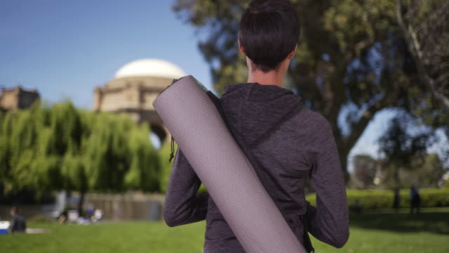 vídeos de stock e filmes b-roll de healthy black woman with yoga mat in park waiting for class to start - san francisco