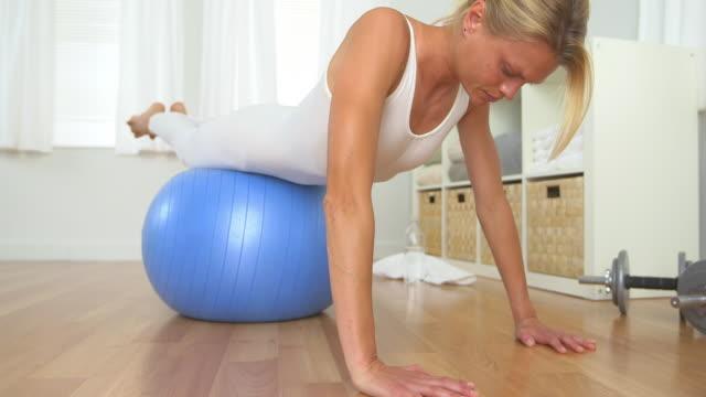 vídeos y material grabado en eventos de stock de healthy blonde woman doing push ups with balance ball - entrenamiento sin material