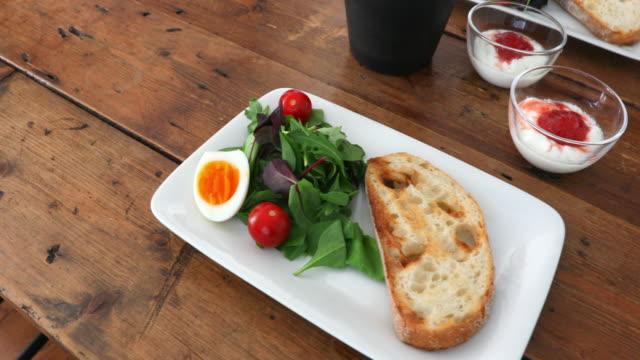 vídeos y material grabado en eventos de stock de desayuno saludable de huevos, ensalada, tomates, tostadas, jugo y yogur - zumo de naranja
