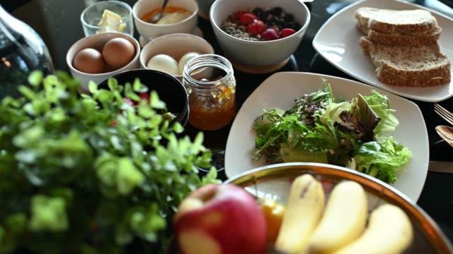 vídeos y material grabado en eventos de stock de desayuno saludable con naranja de frutas, fresa, verduras, plátano, huevos, pan tostado, manzana de yogur y mermeladas en la mesa del comedor - frescura