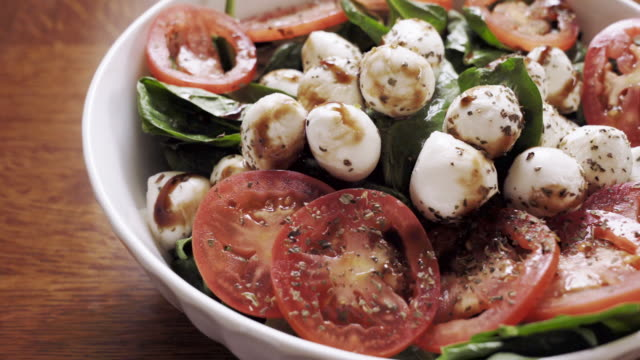 a healthy caprese salad, spinach, sliced tomatoes and fresh mozzarella cheese drizzled in balsamic vinegar - vinegar stock videos & royalty-free footage