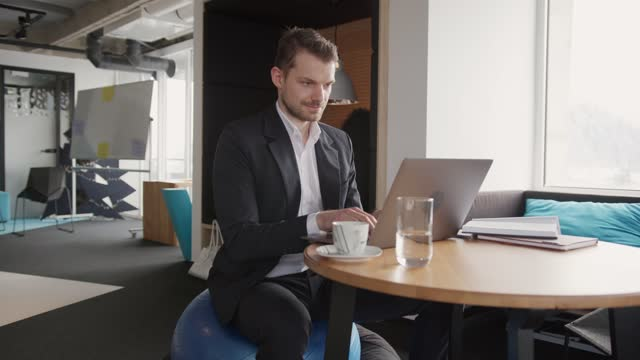 vídeos y material grabado en eventos de stock de empresario caucásico sano sentado en una pelota de yoga mientras trabaja en un ordenador portátil - equilibrio vida trabajo