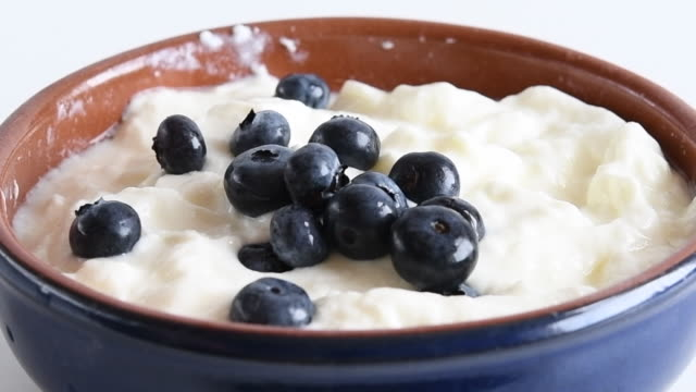 healthy eating: blueberries falling in natural yogurt - vitamin a nutrient stock videos and b-roll footage