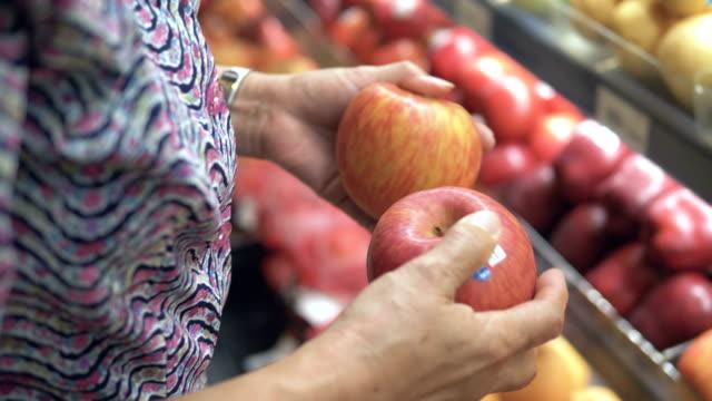 Healthy Eating : Senior woman choosing some apples in supermarket.