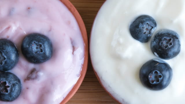 healthy eating: yogurt servings garnished with fresh blueberries. - yoghurt stock videos and b-roll footage