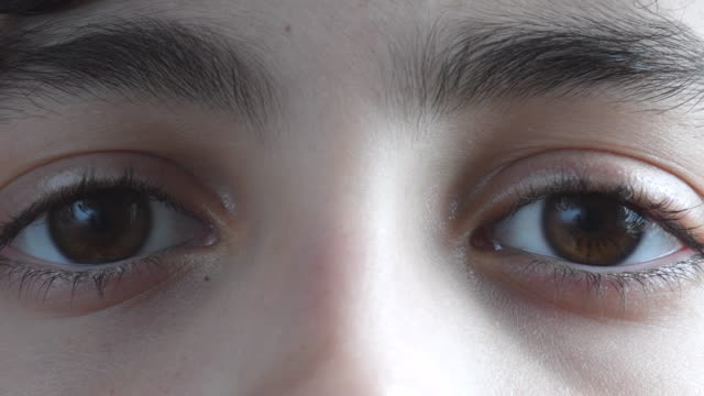 Healthy  eyes of child boy close up. He has a light brown pupil. He blinks and moves the eyelashes.
