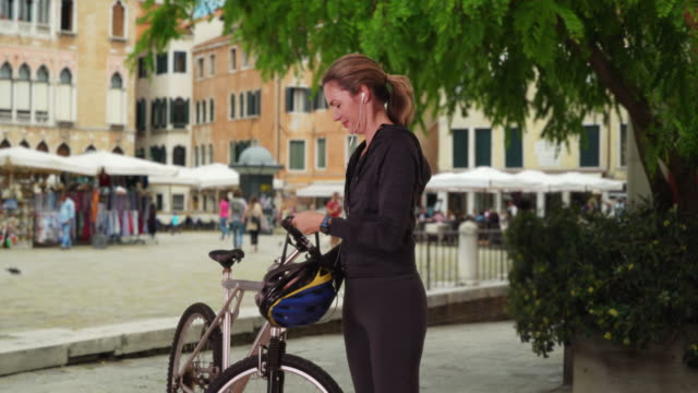 vidéos et rushes de healthy female cyclist in venice preparing for bike ride outside - motard
