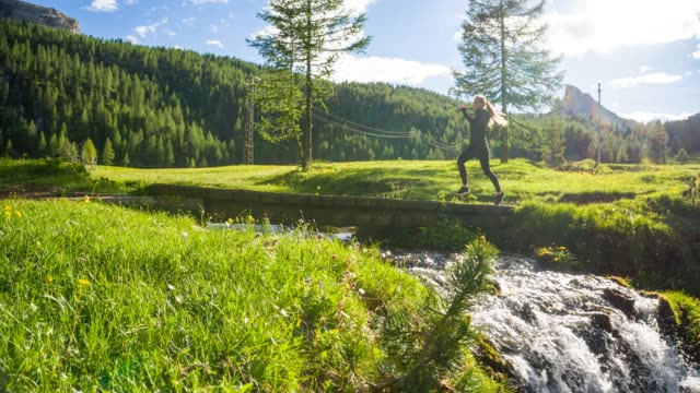healthy fitness woman running outdoors in nature across a bridge over mountain stream on beautiful sunny day - woodland stock videos & royalty-free footage