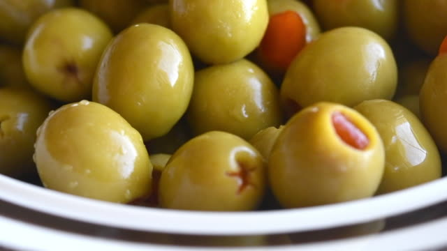 healthy food ingredients: putting stuffed green olives in a deep plate, slow motion - pickled stock videos and b-roll footage